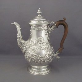 A fine quality antique George IV sterling silver coffee pot by George King, hallmarked London 1824. Baluster shaped, with scroll