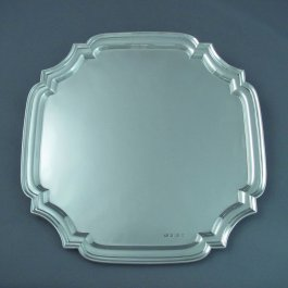 An English sterling silver salver by Charles Usher, hallmarked Sheffield 1934.  Square shape with applied molded border, no feet.