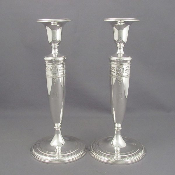 A pair of sterling silver candlesticks by Tiffany & Co., New York c. 1907-47. Neoclassical style, round sconces, bases and tapered
