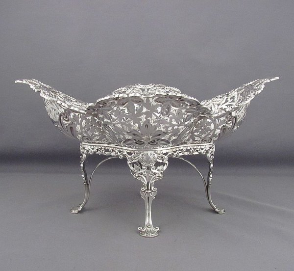 An Edwardian sterling silver dessert stand by James Dixon & Sons, Sheffield 1903. Pierced oval dish on four ornate shell and scroll