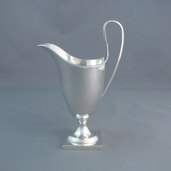 A George III style sterling silver cream jug by CJ Vander, hallmarked London 1969. Inverted helmet shape on square pedestal base with