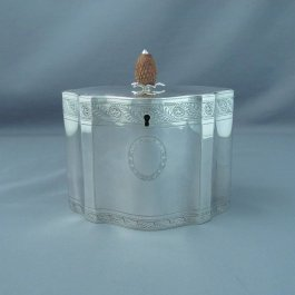 A George III silver tea caddy by Hester Bateman, hallmarked London 1785.  Shaped drum oval with flat lid and engraved with