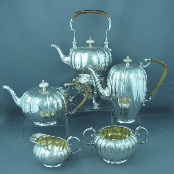 A fine quality English sterling silver tea set by Elkington & Co, hallmarked Birmingham 1915-1928.  George II style, melon shaped with