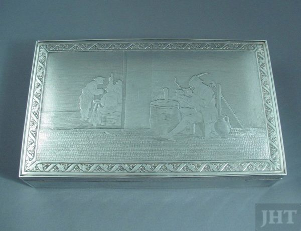 A French .950 silver cigar box c. 1925. Rectangular shape with acid etched smoking scenes on the lid and engine turned sides, wooden