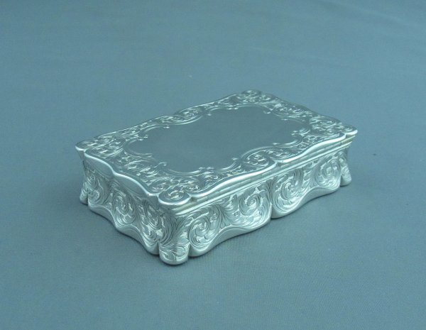 An early Victorian sterling silver table snuff box hallmarked Birmingham 1851 by Edward Smith. Rectangular with scroll edges and