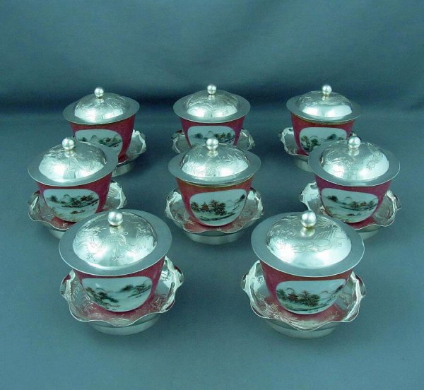 A set of eight Chinese Export Silver and porcelain tea cups by Tack Hing, Hong Kong c. 1920. Silver bases and lids engraved with dragons and