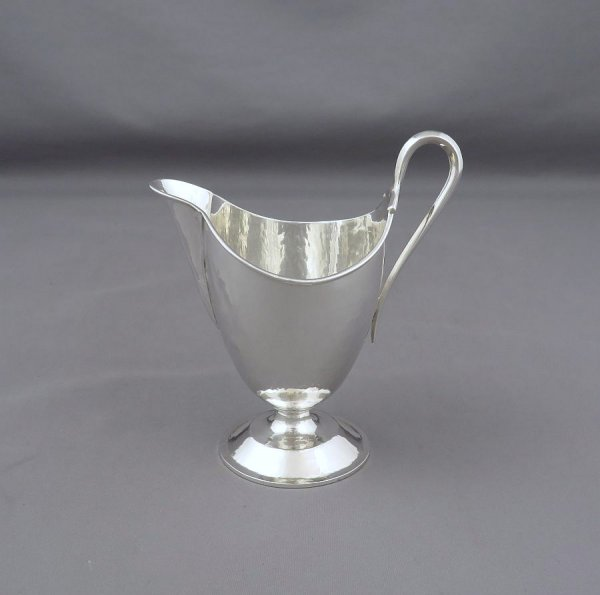 An English sterling silver cream jug by Omar Ramsden, hallmarked London 1935. Tapering cylindrical body on spreading foot with