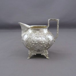 A German .800 silver cream jug by Karl Sohnlein & Sohne, Hanau c. 1900. Oblong shape on four legs with ornate Rococo decoration.