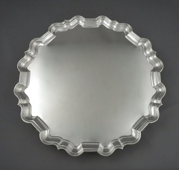 A large George V sterling silver salver by Thomas Bradbury & Sons, hallmarked Sheffield 1928. Circular, with applied scroll border on four