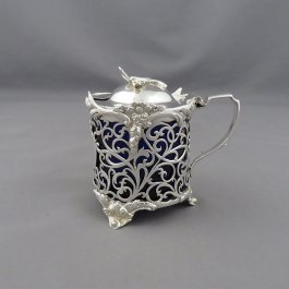 A Victorian sterling silver mustard pot by William Hunter, hallmarked London 1861. Drum shaped with pierced sides and applied