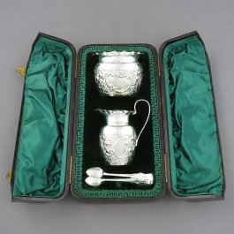 A Victorian sterling silver cream and sugar by Stokes & Ireland Ltd, hallmarked Chester 1897. Round with repoussé decoration, loop