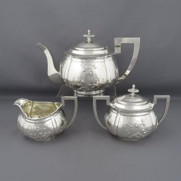 A Chinese Export Silver tea set by Zeesung, Shanghai c.1910. Comprising a teapot, cream jug, and lidded sugar bowl beautifully chased