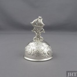 A sterling silver table bell by Friedrich Reusswig, Hanau c. 1900. Hemispherical shape with embossed and chased decoration and a
