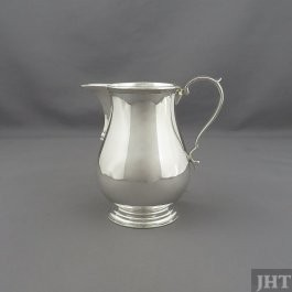An English sterling silver milk jug by Edward Barnard, hallmarked London 1947. Baluster shaped with a sparrow beak, after a George II